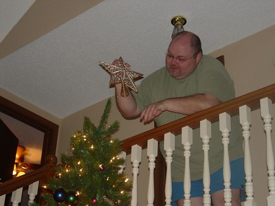 Jon tops the tree with a sparkly star.