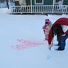 Spraying colored water on the snow.