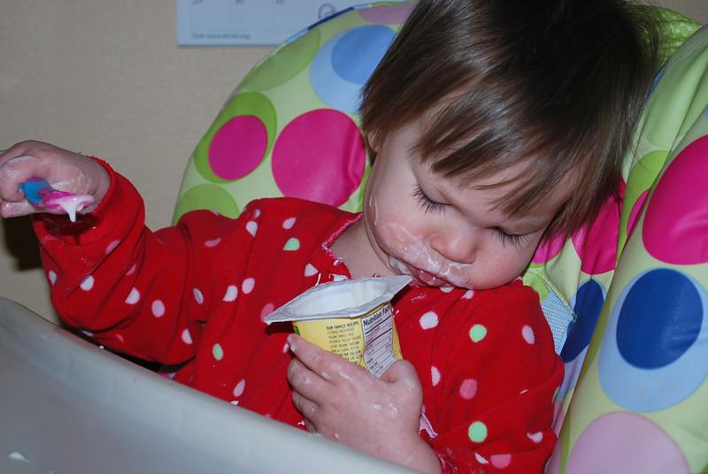 Eating yogurt all by herself.