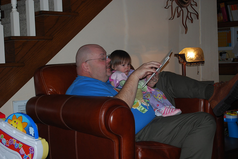 Listening to Papa read her bedtime stories.