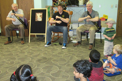 "(From Left) Lisle Mayor Joe Broda, Will Savage, and Senator Michael Connelly lead a storytime at Lisle Library on April 18. Broda and Connelly were acting as ""Honorary Librarians"" in celebration of National Library Week.  Photographer's Name: Nicole Mueller Photographer's City and State: Lisle, IL"