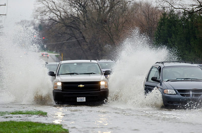 Traffic takes a chance crossing a flooded roadway near the intersection of Midwest Road and Mockingbird Lane in Oak Brook  Photographer's Name: Tristan Zeier Photographer's City and State: Willow Springs, IL