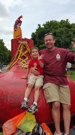 Mark and his son wave to everyone as the Ride with Ronald on the Float<br /> <br /> Photographer's Name: julie travers<br /> Photographer's City and State: elmhurst, IL