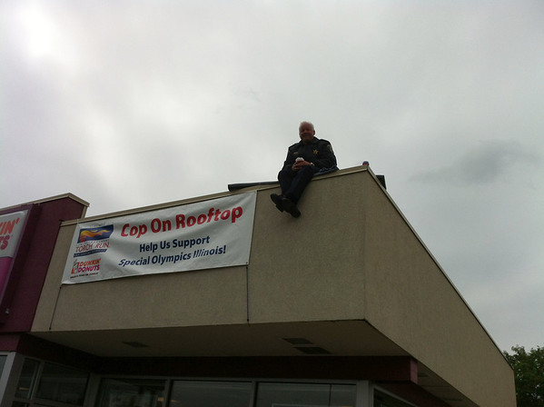 St. Charles Police Chief Jim Lamkin sits atop the roof of Dunkin' Donuts in St. Charles on Friday to raise money for Special Olympics Illinois.<br /> <br /> Photographer's Name: Mike Van Der Harst<br /> Photographer's City and State: St. Charles, IL