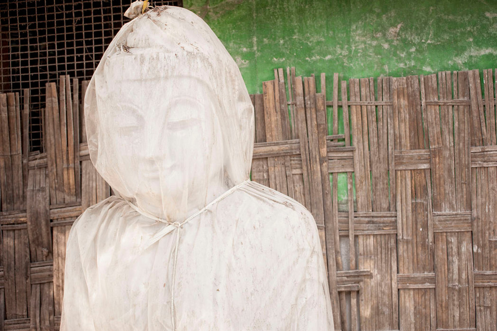 The serene expression of a finely carved Buddha is visible beneath its muslin wrapping.