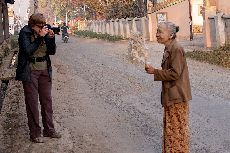 Judy photographs a lady bringing flowers to the temple, Nyaungshwe.