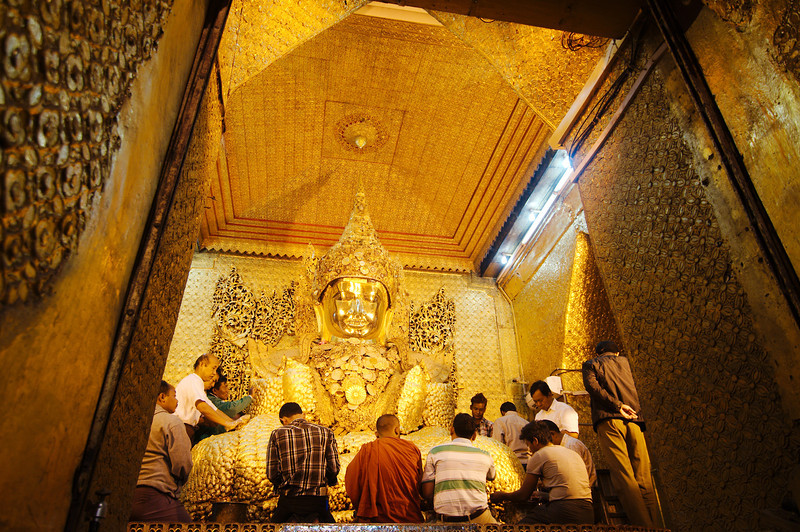 Only men can approach the Mahamuni Buddha and apply gold leaf to its base