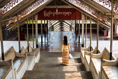 A young woman in traditional dress walks down the many steps towards the bottom of Mandalay Hill
