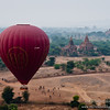 Balloon landing in a field, with the ruins of Old Bagan in the background. - Myanmar