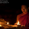 Young Buddhist monk lighting candles in one of the many ancient temples in Old Bagan, Myanmar