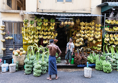 A shopkeeper stands outside his banana shop with his colleague, Yangon, Myanmar