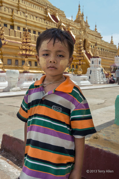 """Portrait of a young boy at Shwezigon Pagoda, Hyuang Oo, Myanmar<br /> <br /> Re comments about the stuff on his face: Thanaka is a cosmetic paste made from the ground bark from the Thanaka tree that is widely used in Myanmar, mostly by women and children. It smells something like sandalwood and has a number of beneficial properties including protection from sunburn, preventing acne and promoting a smooth, beautiful skin.<br /> <br /> Shwezigon Pagoda is one of the oldest of ancient Bagan.  It was completed by King Kyanzittha in 1089 to house a tooth relic  and hairs of the Buddha. It is the most important reliquary shrine (meaning built to house a Buddha relic) in the Bagan area. Pilgrims from throughout Burma travel here each year in the Burmese month of Nadaw (November-December) to celebrate. This festival includes both elements of pre-Buddhist Nat worship (Nats are pagan anamistic spirits) and Buddhist themes. Shwezigon is thus a center of pilgrimage for both the archaic shamanic culture of Burma and the newer religion of Buddhism.<br /> <br /> Other photos from around the temple can be seen here: <a href=""""http://goo.gl/Wb5hH"""">http://goo.gl/Wb5hH</a>"""