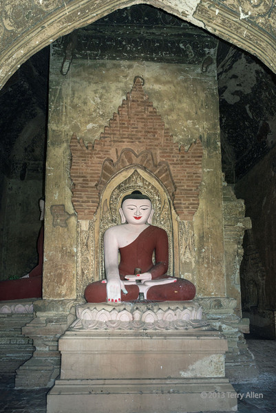 Buddha image in temple-2 alcove, Bagan, Myanmar<br /> <br /> The hand positions of all Buddhas have symbolic meaning.  The hand positions here is the Bhumisparshra Mudra. This hand position of 'touching the earth' or 'calling the earth to witness' commemorates Siddhartha Gautama Buddha's victory over temptation by the demon Mara (equivalent to Satan).