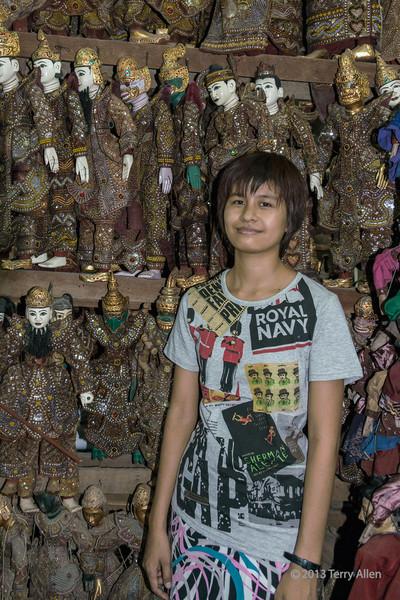 Shop girl with rows of Burmese puppets, Mandalay, Myanmar