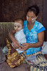Woman with a child applying gold leaf to an ornament, Mandalay, Myanmar
