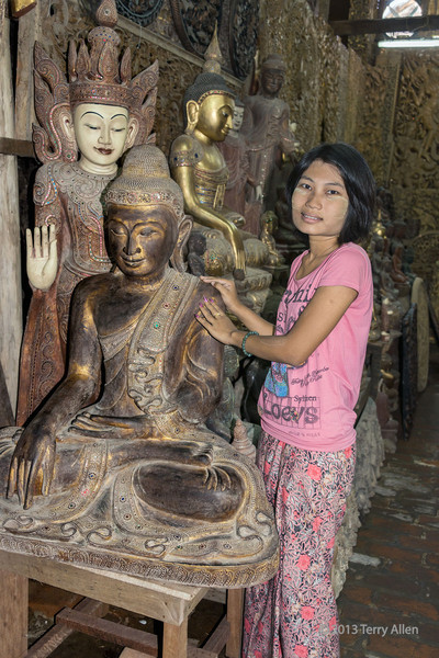 Burmese shot girl with a Buddha statues and a kinnayi behind the Buddha.<br /> <br /> A kinnayi (kinnari) has the head, torso, and arms of a woman and the wings, tail and feet of a swan, and is a traditional symbol of feminine beauty, grace and accomplishment.