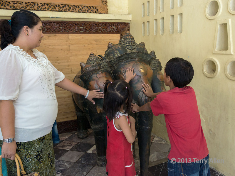 Family rubbing the three headed Khmer bronze elephant for its healing properties, Mahamuni Buddha Temple, Mandalay, Myanmar