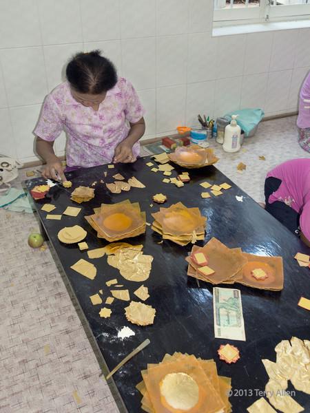 Women gold worker preparing stacks of gold leaf, King Galon Goldsmith, Mandalay, Myanmar