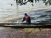 Bailing out her dugout canoe.<br /> <br /> On the road from Bagan to Mandalay recent heavy rains had flooded the area, and the only high ground was the road itself.  This woman was trying to get her canoe floating again.  The action is best seen at larger sizes.