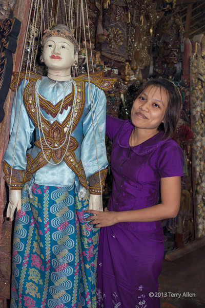 "Holding hands with a large puppet<br /> <br /> Burmese shop girl with a large marionette, Mandalay, Myanmar<br /> <br /> The use of Burmese marionettes for entertainment dates back to the 18th century with the same set of 27 characters still in use today.  The marionette puppetry troupes are called Yoke the. Men puppets are controlled by 18 wires and female puppets by 19 wires, each controlled by a single person (You can count the 19 wires on this female puppet).  Marionettes, besides being used for entertainment, could be used to impart information or political discontent since the puppets could say things that a human would be punished for by death.<br /> <br /> Some other photos of these fascinating puppets, a Burmese xylophone, and a kinaree (mythical female figure) can be seen here: <a href=""http://goo.gl/aXGPMn"">http://goo.gl/aXGPMn</a><br /> <br /> The rich colour and detail of these photos is best appreciated at larger sizes<br /> <br /> 5/2/14  <a href=""http://www.allenfotowild.com"">http://www.allenfotowild.com</a>"