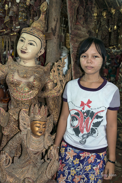 Burmese shop girl with a statue of a kinaree (mythical female figure that is part bird), Mandalay, Myanmar