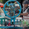 Street-vendor-pressing-sugar-cane-juice-(guarapo),-Irrawaddy-River-docks,-Yangon,-Burma