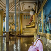 Nun-praying-by-statue-of-Buddha,-Schwedagon-Pagado,-Yangon,-Burma