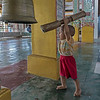 Young boy hitting bell, Reclining Buddha Shrine, Yangon, Burma