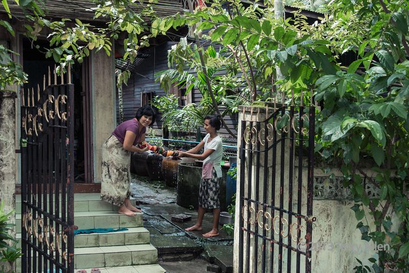 Women wringing out laundry, Dala village, Myanmar