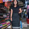 Woman demonstrating a longyi from her shop, Scott Market, Yangon, Burma