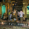 Family-anointing-Buddha-at-night,-Schwedagon-Pagoda,-Yangon,-Burma
