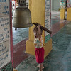 Young-boy-trying-to-hit-bell,-Reclining-Buddha-shrine,-Yangon,-Burma<br /> <br /> This little guy struggled mightily to get the heavy wooden pole up to where he could use it to hit the prayer bell