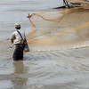 Fisherman-fishing-with-a-cast-net,-Irrawaddy-River-docks,-Yangon,-Burma