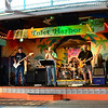 Need help...... I always have trouble getting clear pictures indoors when I don't use flash.This picture is very grainy and the focus is off. I was using my 18-105 lens , VR was on and there was plenty of ambient light. This was taken out on the rear deck of the marina. Is it possible the vibration from the bands speakers would cause this , (my ears are still ringing this morning! )I was only about 15 feet from the stage. I tried the camera on several different settings and they all pretty much come out the same. Since we were seated on a pier out over the water the floors would also vibrate when any one would walk close or boats would go by. Usually the VR does a pretty good job of canceling that out.. Anyone got any ideas on how I can get sharper images...thanks
