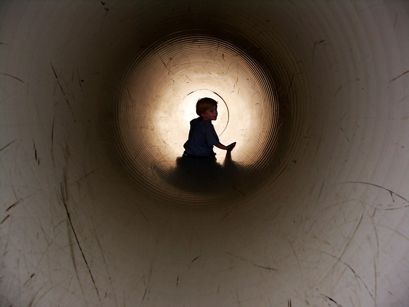 A boy looks back from the base of a tunnel slide.