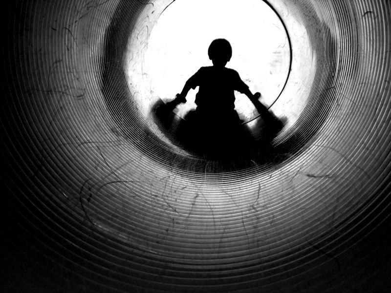 Dramatic silhouette of a child in a tunnel slide.