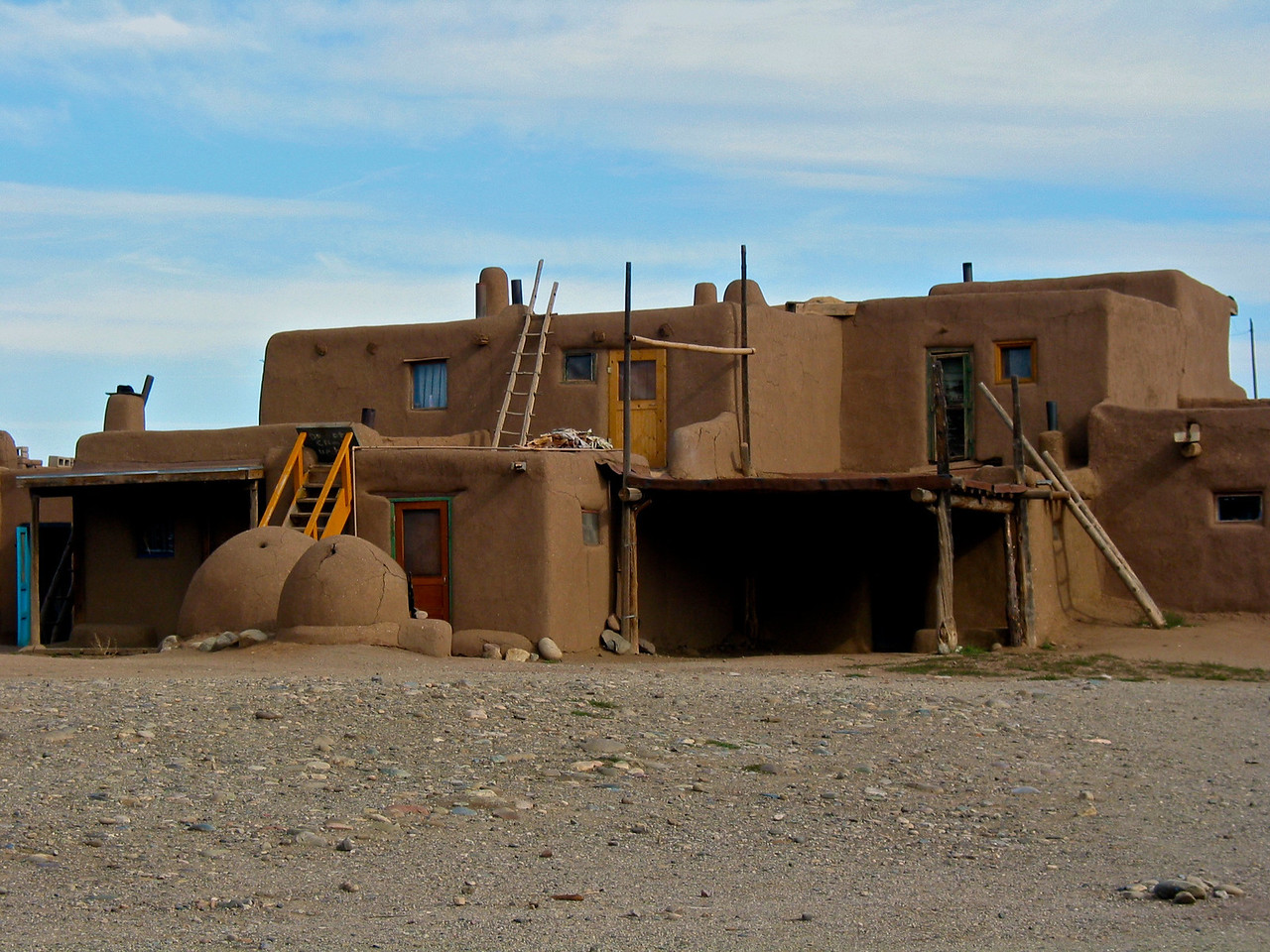 The Pueblo is made entirely of adobe -- earth mixed with water and straw, then either poured into forms or made into sun-dried bricks. The walls are frequently several feet thick. The roofs of each of the five stories are supported by large timbers -- vigas -- hauled down from the mountain forests. Smaller pieces of wood -- pine or aspen latillas -- are placed side-by-side on top of the vigas; the whole roof is covered with packed dirt.