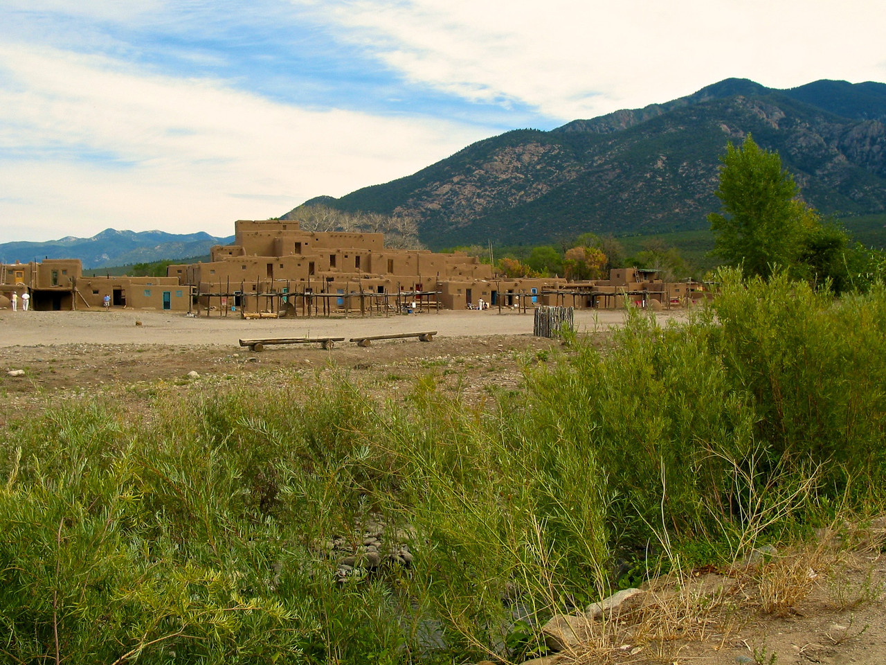 Taos Pueblo's most prominent architectural feature is a multi-storied residential complex of reddish-brown adobe divided into two parts by the Rio Pueblo. According to the Pueblo's Web site, it was probably built between 1000 and 1450 A.D. It was designated a National Historic Landmark on October 9, 1960, and in 1992 became a World Heritage Site. As of 2006, about 150 people live in it full-time.