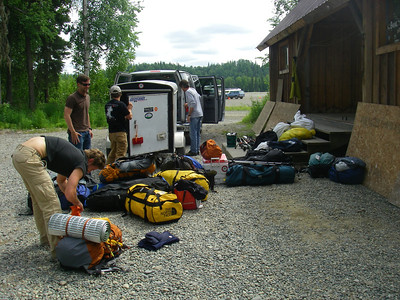 At Talkeetna airport (50 ft). For our guide, Dyrny, it is going to be  the 18th Denali summit attempt; for co-guide, Doug, the 4th. Doug is next to trailer with black T-shirt. From left: Tim, John W, Doug, and John DM.