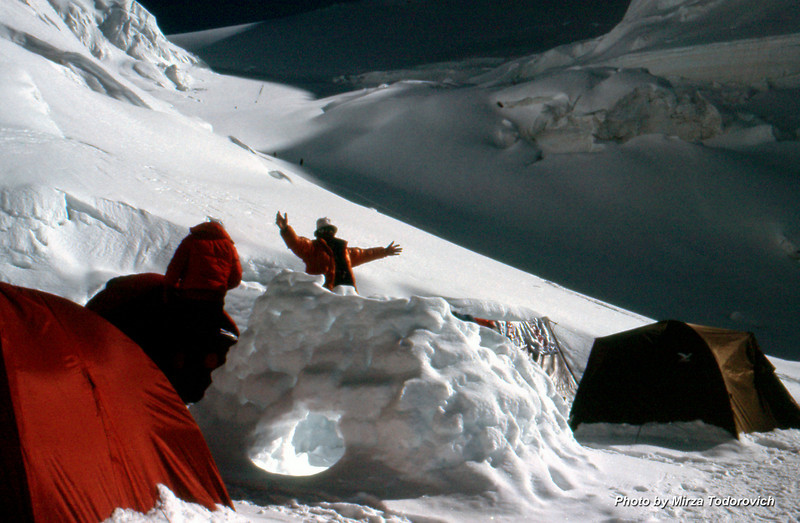 Camp 2, Hamo is greeting the sun and mountains. Far, behind him, climbers slow going up towards Camp3.