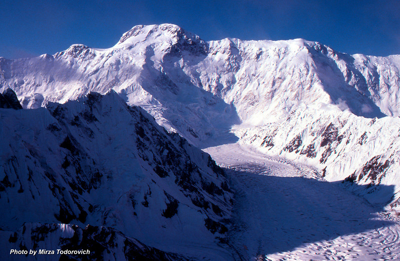 The clear morning view on Peak Pobeda (7439m) on the border between China and Kyrgyzstan. On the left side from the main peak is East Summit (6762m), on the right side is West Summit (6918m). There are multiple routes from BC Peak Pobeda located on the Zvezdochka glacier to the main summit. Peak Pobeda, by far the most difficult peak in region, is first climbed by Russian climber V. Abalakov and his team in 1956.