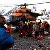 """Helicopter is here to take us down the hill and back to """"civilization"""". As Gafa is checking settings on his camera, Hamo, far back in orange down jacket, is waiting to board."""