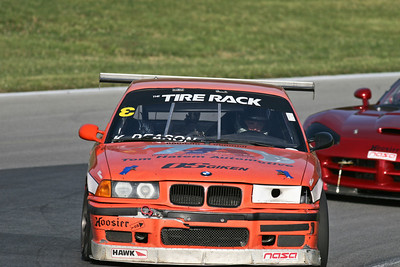 Korey Deason and his NASA German Touring Series (GTS3)  BMW M3 (orange #571) in action at Mid-Ohio Sports Car Course, July 2010