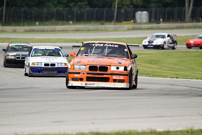 Korey Deason and his NASA German Touring Series (GTS3)  BMW M3 (orange #571) in action at Mid-Ohio Sports Car Course, August 2010