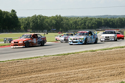Korey Deason (orange BMW #571) leads the GTS class into the Keyhole at Mid-Ohio on his way to another NASA Great Lakes Region win at Mid-Ohio Sports Car Course, July 2010