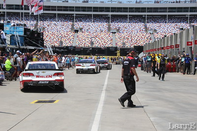 cars leave garage area  and head to the track.