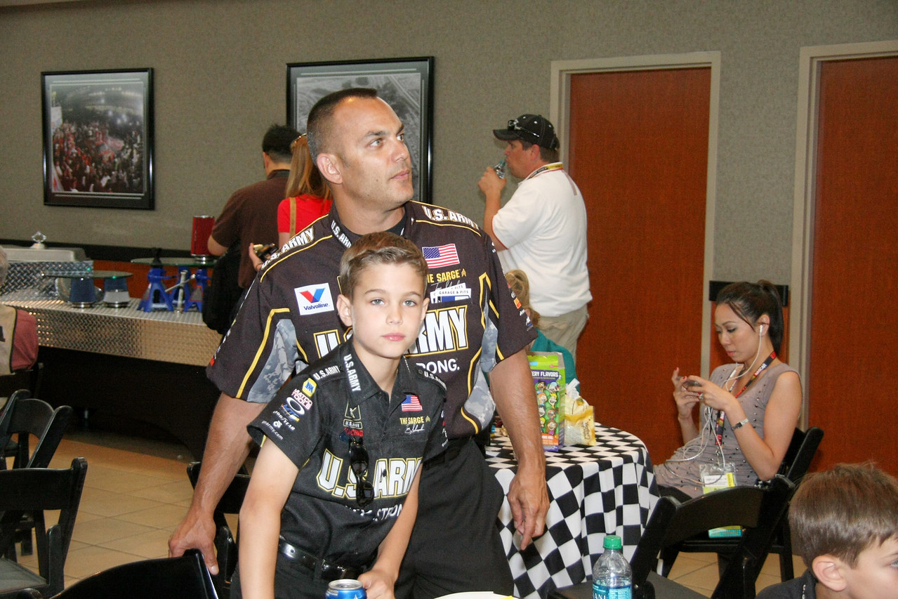 Schumacker and son watch pre-race TV in the media center