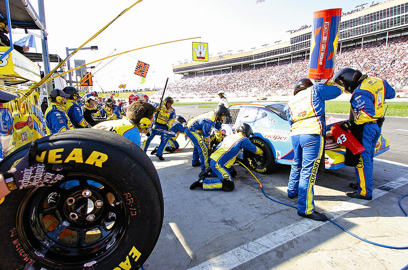 Bobby Labonte's pit crew scrambles to get him back out onto the track after a tire change and fuel up Sunday during the Kobalt Tools 500.