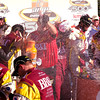 NASCAR Sprint Cup Driver Clint Bowyer on Victory lane After Winning AMp Energy Juice 500 at Talladega.  Champagne was flying.  Everyone, to Include the Sprint Girl Got Wet.  Only the NASCAR Official was Smart Enough to Keep on His Safety Gear.