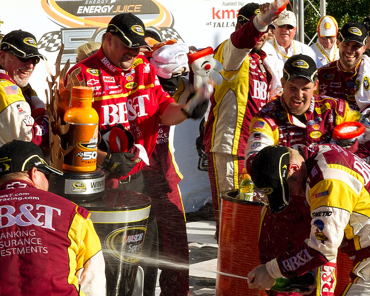 NASCAR Sprint Cup Driver Clint Bowyer on Victory lane After Winning Amp Energy Juice 500 at Talladega Firing a Stream of Champagne at Team.